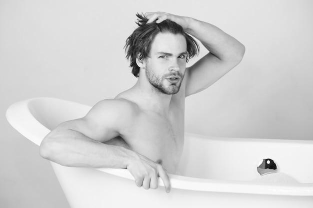 Przystojny mężczyzna siedzi w wannie. facet w wannie. spa i uroda, relaks i higiena, opieka zdrowotna. czarny biały.