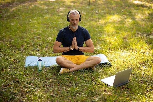 Przystojny mężczyzna słucha medytacji w słuchawkach w przyrodzie