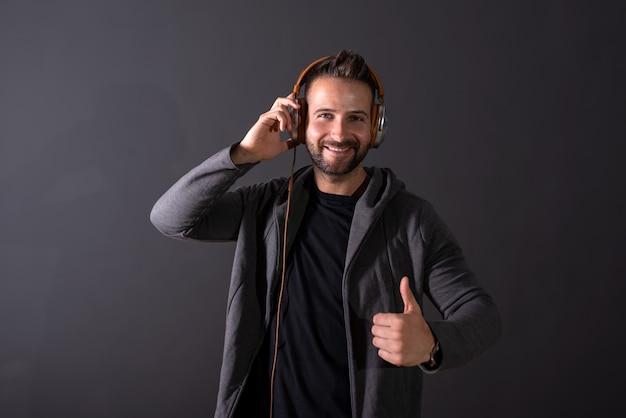 Przystojny mężczyzna słucha muzyki i pokazuje kciuk do góry