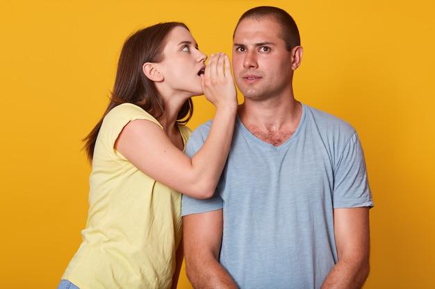 Przystojny mężczyzna słucha uważnie swojej dziewczyny, jest ciekawy, stoi prosto. aktywna energiczna młoda kobieta mówi tajemnice