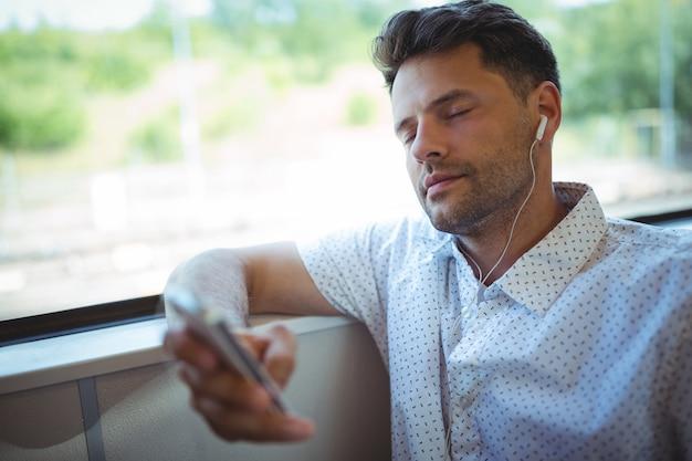 Przystojny mężczyzna słuchania muzyki na telefon komórkowy