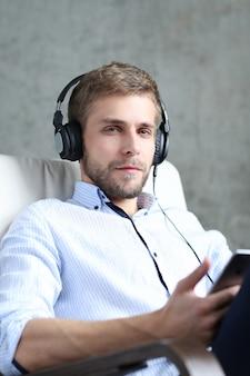 Przystojny mężczyzna słuchania podcastu na słuchawkach