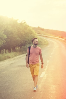 Przystojny mężczyzna spaceru na drodze wsi. filtr retro vintage instagram