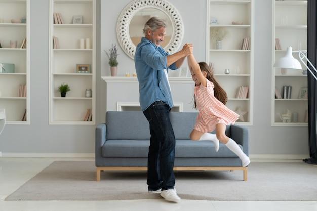 Przystojny mężczyzna spędza czas w domu ze swoją śliczną córeczką. szczęśliwego dnia ojca! tata i córka.
