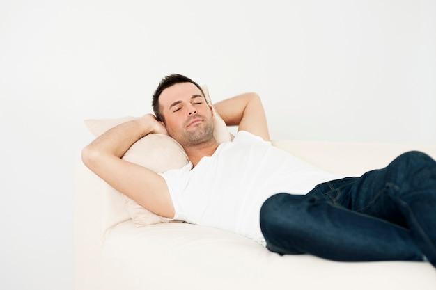 Przystojny mężczyzna śpi na kanapie