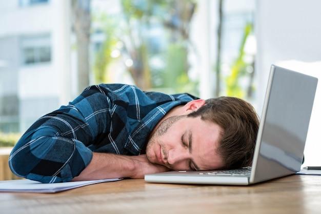 Przystojny mężczyzna śpi na laptopie w jasnym biurze
