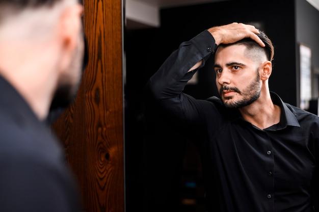 Przystojny mężczyzna sprawdza jego nowego włosianego styl
