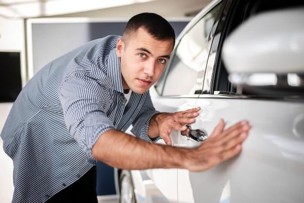 Przystojny mężczyzna sprawdza samochód