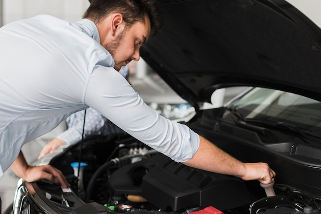 Przystojny mężczyzna sprawdza samochodowego silnika