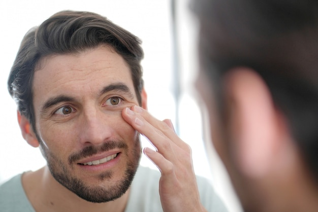 Przystojny mężczyzna sprawdza zmarszczenia w lustrze w domu