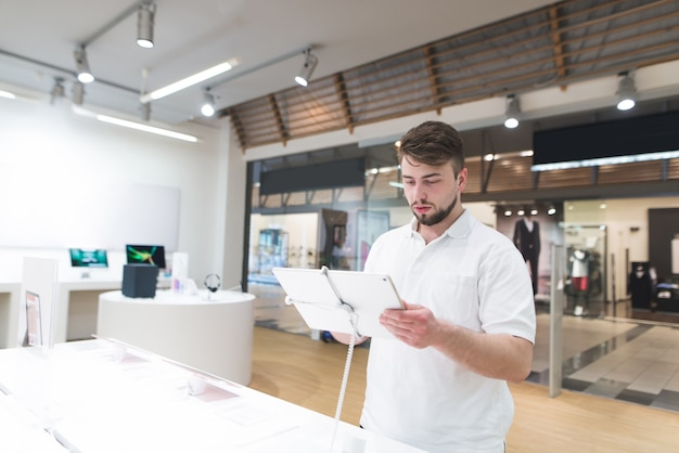 Przystojny mężczyzna stoi z tabletem w ręku w nowoczesnym sklepie technologicznym