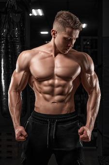 Przystojny mężczyzna stojący mocno na siłowni i napinający mięśnie muskularny atletyczny kulturysta fitness