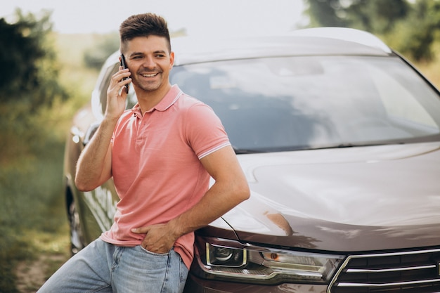 Przystojny mężczyzna stojący przy swoim samochodzie w lesie