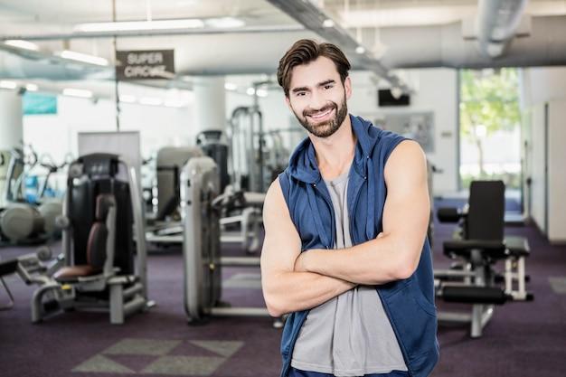 Przystojny mężczyzna stojący z rękami skrzyżowanymi na siłowni