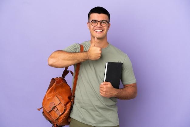 Przystojny mężczyzna student na odosobnionym tle, dając gest kciuka w górę