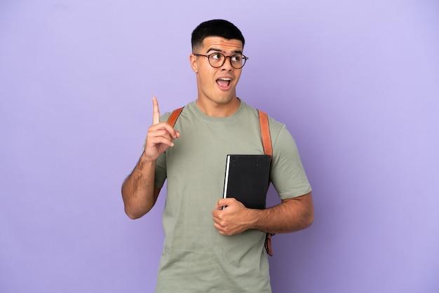 Przystojny mężczyzna student na odosobnionym tle myśli pomysł wskazujący palec w górę