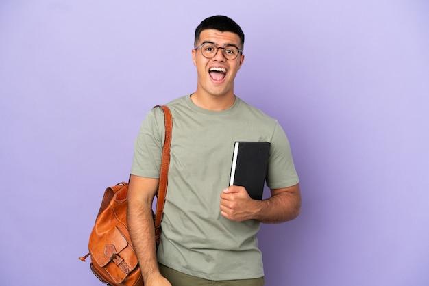 Przystojny mężczyzna student na odosobnionym tle z niespodzianką wyraz twarzy