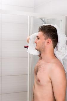 Przystojny mężczyzna suszy mokre włosy czystym ręcznikiem po zabiegach mycia w nowoczesnej, wyłożonej kafelkami łazience
