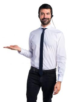 Przystojny mężczyzna telemarketer gospodarstwa coś