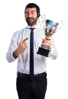 Przystojny mężczyzna telemarketer posiadający trofeum