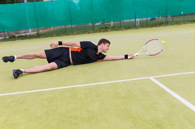Przystojny mężczyzna tenisista ubrany w odzież sportową w akcji podczas gry spadł na korcie