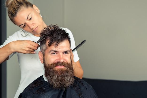 Przystojny mężczyzna tnie i goli brodę i wąsy. hipster klient odwiedzający fryzjera. stylizacja i cięcie brody.
