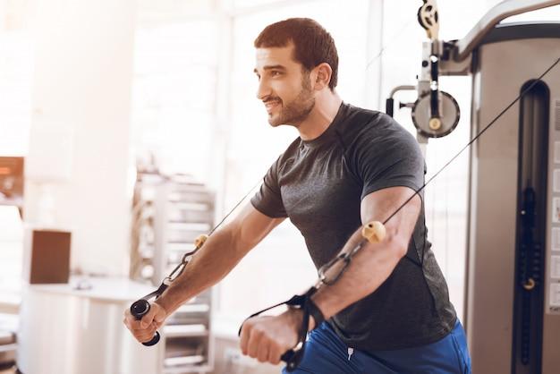 Przystojny mężczyzna trenuje na siłowni.