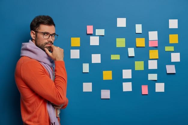 Przystojny mężczyzna trzyma brodę, nosi modne ubrania, stoi z notatnikami, patrzy przez okulary, myśli nad biznesplanem