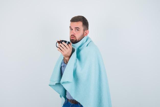 Przystojny mężczyzna trzyma filiżankę herbaty w obu rękach w koszuli, dżinsach, szal i patrząc wyczerpany. przedni widok.