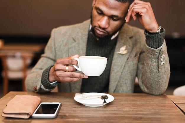 Przystojny mężczyzna trzyma filiżankę z kawą