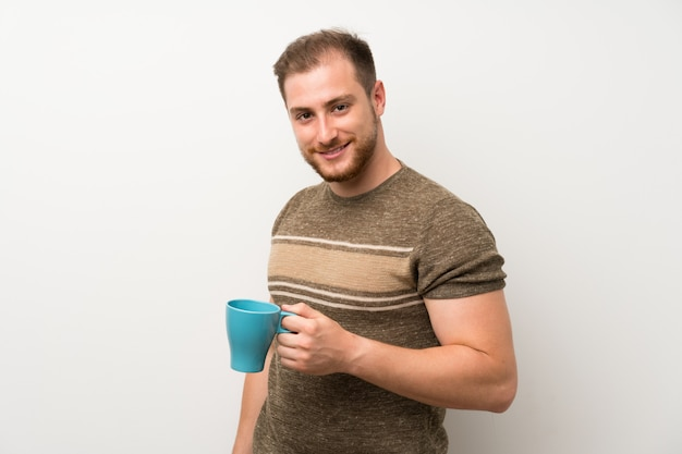 Przystojny mężczyzna trzyma gorącą filiżankę kawy