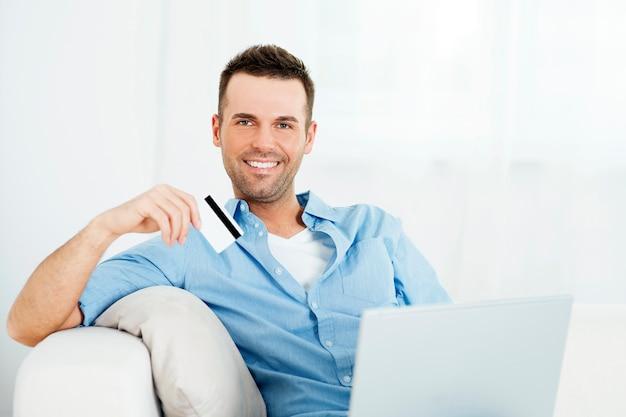 Przystojny mężczyzna trzyma kartę kredytową i za pomocą laptopa