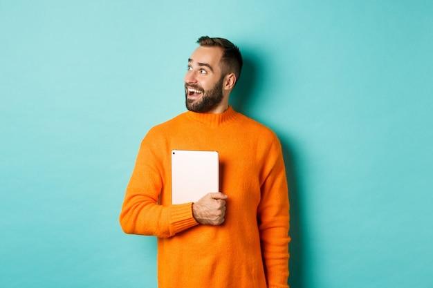 Przystojny mężczyzna trzyma laptopa, patrząc w lewo ze zdziwieniem i zdumieniem, stojący w pomarańczowym swetrze