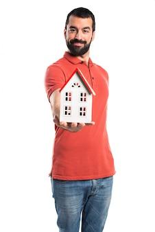 Przystojny mężczyzna trzyma mały dom