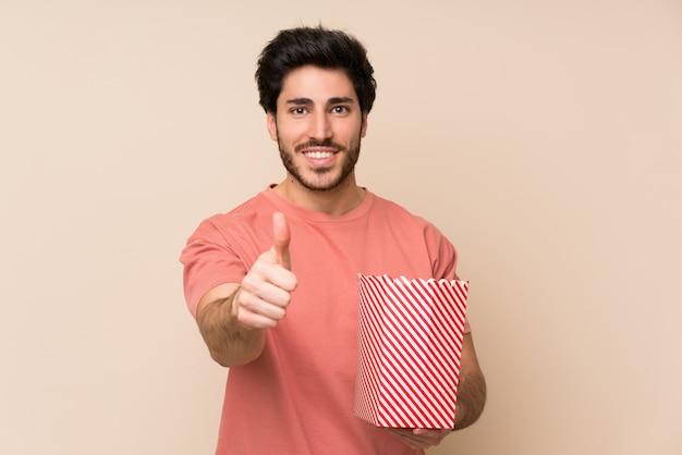 Przystojny mężczyzna trzyma miskę popcorns