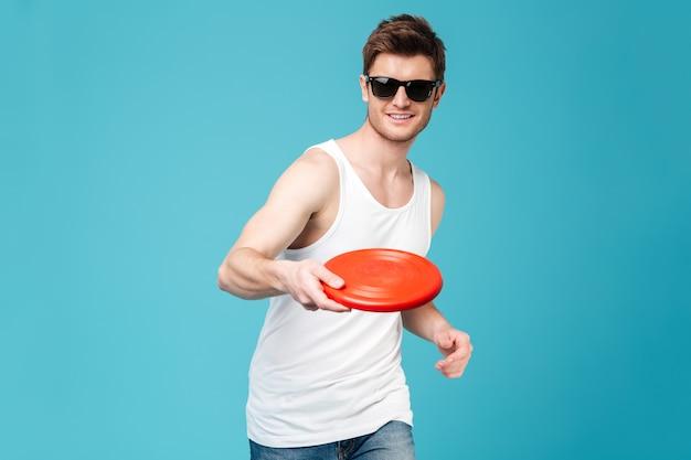 Przystojny mężczyzna trzyma plażową lato zabawkę.