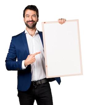 Przystojny mężczyzna trzyma puste plakietkę