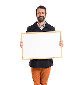 Przystojny mężczyzna trzyma pusty tabliczkę