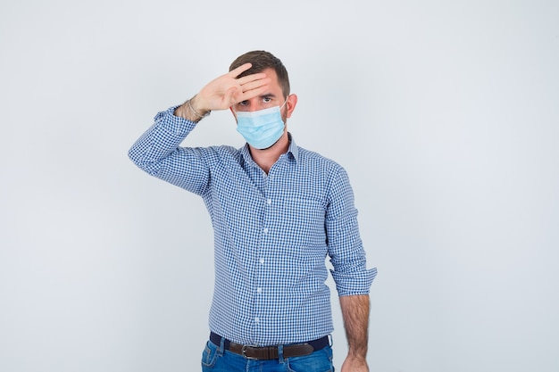 Przystojny mężczyzna trzyma rękę na głowie, sprawdza jego temperaturę w koszuli, dżinsach, masce i wygląda na wyczerpanego. przedni widok.