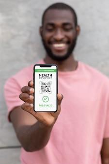 Przystojny mężczyzna trzyma smartfona z kodem qr na ekranie