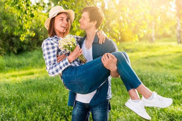 Przystojny mężczyzna trzyma szczęśliwej kobiety na rękach