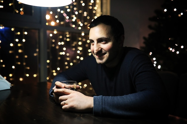 Przystojny mężczyzna trzyma szklankę alkoholu z lodem w nocnym klubie