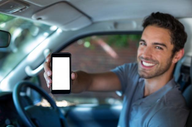 Przystojny mężczyzna trzyma telefon w samochodzie