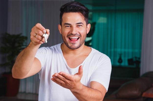 Przystojny mężczyzna trzyma w ręku klucz do nowego domu.