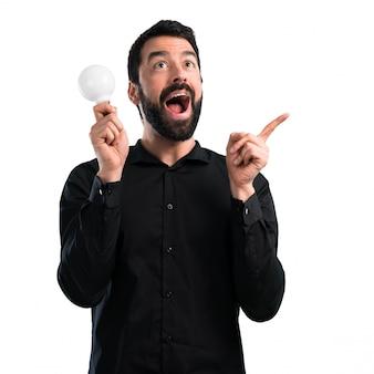Przystojny mężczyzna trzyma żarówkę na białym tle z brodą