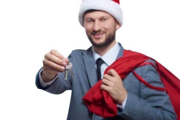 Przystojny mężczyzna ubrany jak święty mikołaj dający kluczyk do samochodu lub domu