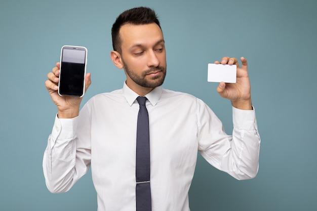 Przystojny mężczyzna ubrany w codzienne ubrania na białym tle na tle ściany trzymając i przy użyciu telefonu