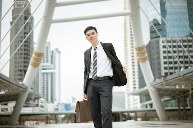 Przystojny mężczyzna, ubrany w czarny garnitur i białą koszulę, trzyma torebkę i stoi w mieście.