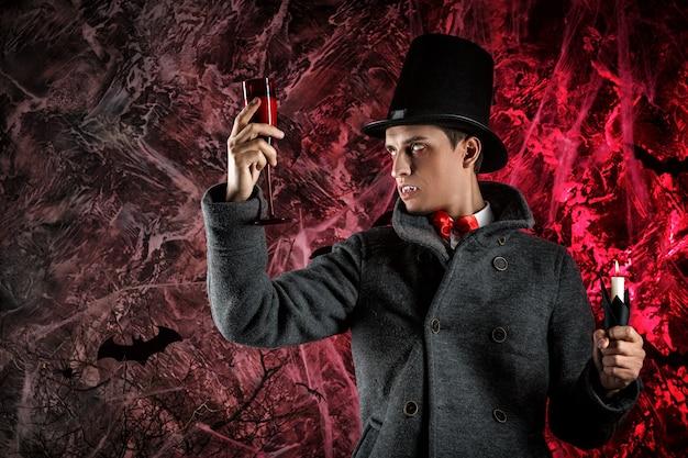 Przystojny mężczyzna ubrany w kostium drakuli na halloween. atrakcyjny wampir patrzy na szklankę krwi
