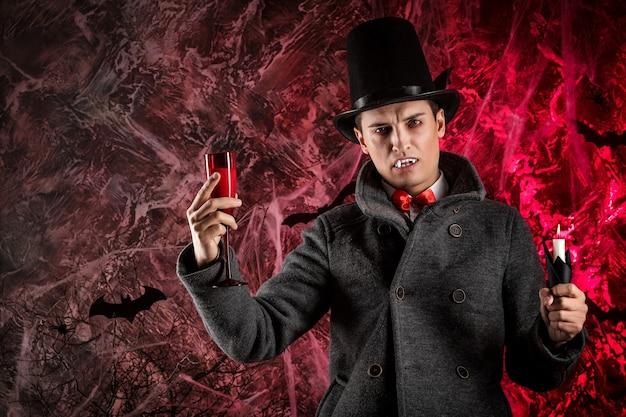 Przystojny mężczyzna ubrany w kostium drakuli na halloween. atrakcyjny wampir trzyma szklankę krwi